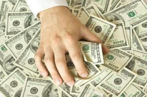 Фото руки на американской валюте (с) http://www.inlandempirerealestatebroker.com